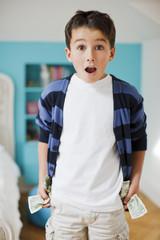 Surprised boy holding dollar bills