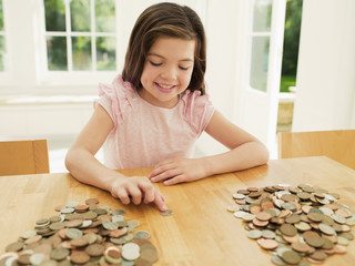 Smiling girl counting coins