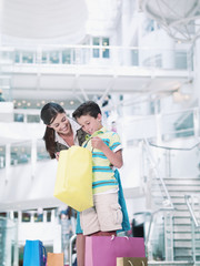 Mother and son looking in shopping bags in mall