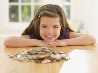 Smiling girl looking at pile of coins