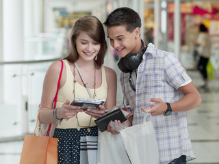 Teenage couple looking at cd rom cases in mall