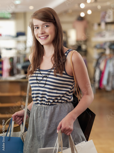 Teenage girl carrying shopping bags in clothing store