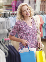 Smiling woman carrying shopping bags in clothing store