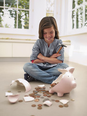 Girl using hammer to break piggy bank