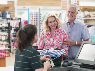 Cashier scanning couple?s purchases in store