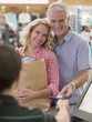 Smiling couple with shopping bag handing credit card to cashier