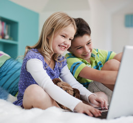 Brother and sister using laptop together