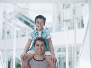 Father carrying son on shoulders in mall