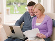 Couple with paperwork using laptop together