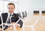 Businessman sitting with model wind turbines in conference room