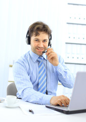Closeup of a businessman with headset. He is working