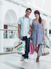 Smiling couple carrying shopping bags in mall