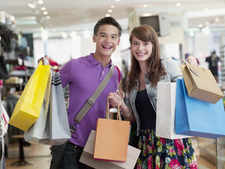 Smiling couple carrying shopping bags in store