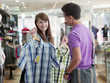 Couple shopping for shirts in store