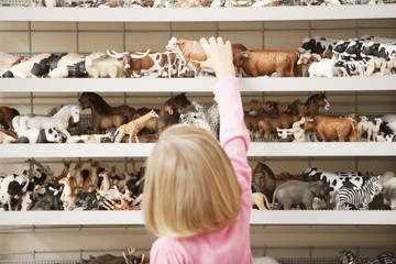Girl reaching for plastic cow in toy store