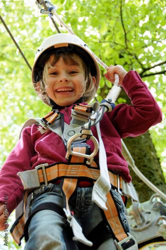 Mädchen mit Helm beim Klettern im Wald