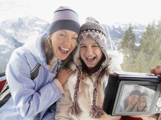 Mother and daughter taking self-portrait on ski lift