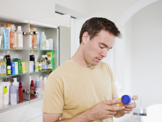Man reading instructions on pill bottle