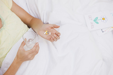 Sick woman in bed taking pills