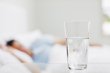 Close up of glass of water with sick man in background