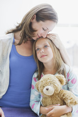 Mother hugging daughter holding teddy bear