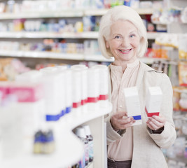 Senior woman comparing packages in drug store
