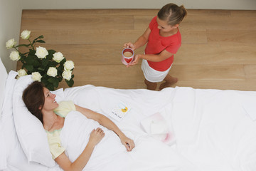 Girl bringing coffee to sick mother in bed