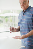 Senior man holding glass of water and pills