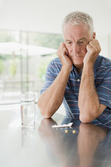 Unhappy man looking at pills on counter