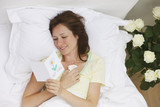 Sick woman laying bed reading get well card