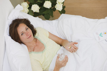 Sick woman laying in bed and taking pills with water