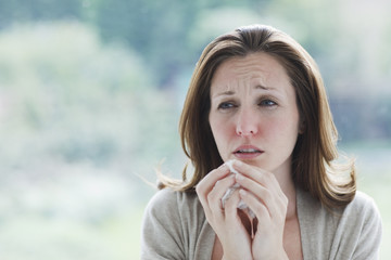 """""""Frowning, sick woman holding tissue"""""""