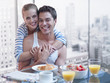 Couple hugging with breakfast on the table