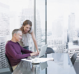 Couple working on computer with cityscape in background