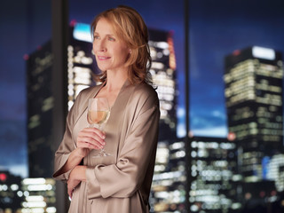 Woman in nightgown drinking white wine at night
