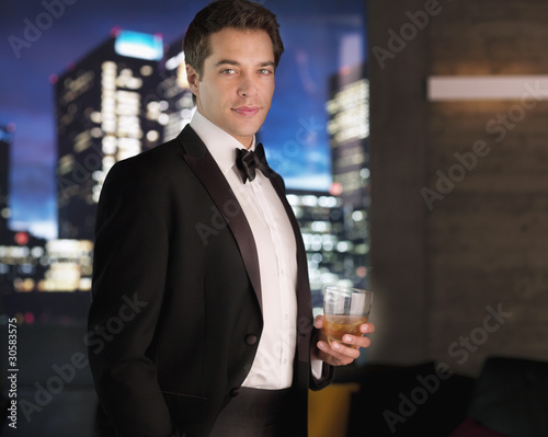 Smiling man in tuxedo drinking cocktail