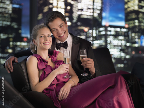 Elegant couple drinking Champagne at night