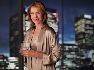 Woman in nightgown drinking with cityscape in background
