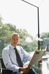 Businessman reading newspaper at desk
