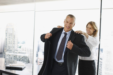 Businesswoman helping co-worker put on coat