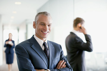 Businessman standing in busy office
