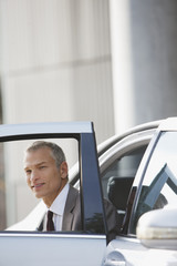 Businessman getting out of car