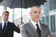 Chauffeur holding umbrella for businessman