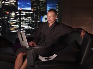 Man in bathrobe working on laptop at night