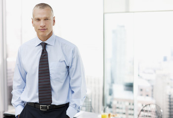 Businessman standing in office with cityscape in background