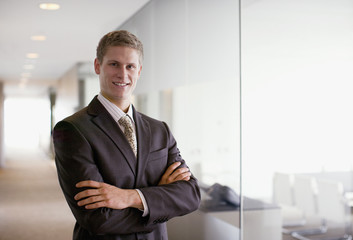 Businessman with arms crossed in office corridor