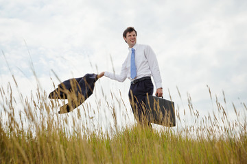 Businessman with briefcase walking through long grass