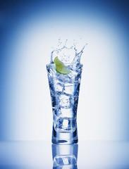 Lime slice splashing water from glass