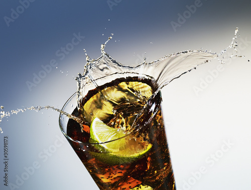 Lime slice splashing soda from glass