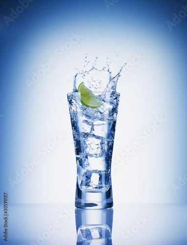 Lime slice splashing water from glass